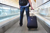 Traveller with a suitcase on the speedwalk — Stock Photo