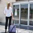 Stock Photo: Girl with suitcase entering airport