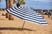 Striped umbrella on the beach — Stock Photo
