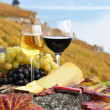 Two wineglasses, cheese and grapes on the terrace of vineyard in - Stock Photo