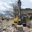 Excavator demolishing an old building - Stock Photo