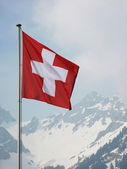 Swiss flag agains snowy Alps — Stock Photo