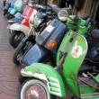 Row of mopeds on a street of Bangkok - Stock Photo
