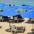Sun umbrellas on a sandy beach against ocean — Stock Photo