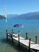 Chair and umbrella on a wooden pier at the lake Thun, Switzerlan — Stock Photo