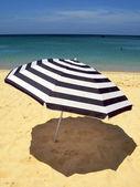 Striped umbrella against sandy beach and ocean — Stock Photo