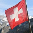 Swiss flag against snowy Alps — Stock Photo