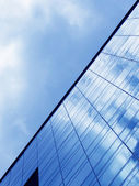 Cloudy sky reflected in the glass wall of a high-rise building — Stock Photo