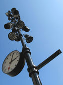 Signpost with a clock and lamp on it — Stock Photo