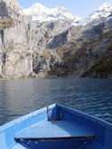 Prow of a boat against surface of Oeschinensee lake and snowy Al — Stock Photo