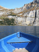 Prow of a boat against surface of Oeschinensee lake and Alps — Stock Photo