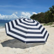 Striped umbrella on a sandy beach of Langkawi island - Stock Photo