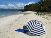Striped umbrella on a secluded beach of Langkawi island, Malaysi — Stock Photo