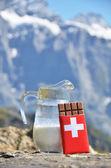 Swiss chocolate and jug of milk against mountain peak. Switzerla — Stock Photo
