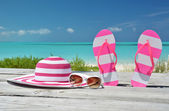 Hat, sunglasses and flip-flops against ocean. Exuma, Bahamas — Stock Photo