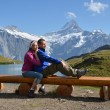Travelers on a bench enjoying Alpine panorama. Jungfrau region,  — Stock Photo