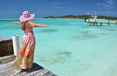Chica en el embarcadero de madera mirando al océano. exuma, bahamas — Foto de Stock