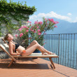 Young woman sunbathing at the Como lake — Stock Photo