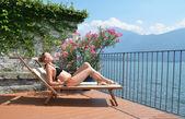 Young woman sunbathing at the Como lake — Stock Photo