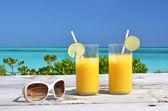Sunglasses and orange juice — Stock Photo