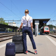 Girl with a suitcase at the train station — Stockfoto