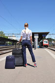 Girl with a suitcase at the train station — Стоковое фото