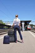 Chica con una maleta en la estación de tren — Foto de Stock