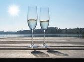 Due bicchieri di champagne contro un lago — Foto Stock