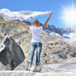 Stock Photo: Girl holding a flapping shawl against Rhone glacier. Switzerland