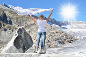 Girl holding a flapping shawl against Rhone glacier. Switzerland — Stock Photo
