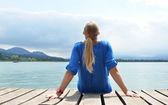 Girl on the wooden jetty. Switzerland — Stock Photo
