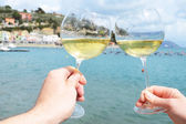 Two wineglasses in the hands against the harbour of Portvenere, — Stock Photo