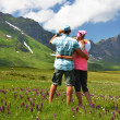 Travelers in an Alpine meadow. Melchsee-Frutt, Switzerland  — Stock Photo