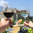 Two hands holding wineglasses against Chateau d'Aigle, Switzerla — Stockfoto