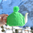 Tea pot in the knotted cap in the hand against mountain scenery  — Stock Photo
