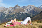 Young woman having rest in Alpine meadow — Stock Photo