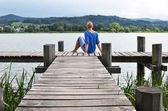 Girl on the wooden jetty — Stock Photo