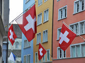 Old street in Zurich decorated with flags for the Swiss National Day — Stock Photo