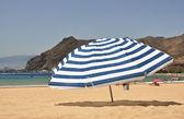Randig paraply på stranden — Stockfoto