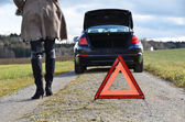 Broken car, girl and warning triangle — Stock Photo