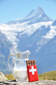 Chocolate and milk against mountain peak — Stock Photo