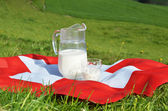 Jug of milk on the Swiss flag. — Stock fotografie