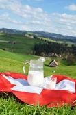 Jug of milk on the Swiss flag — Stock Photo