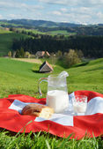 Jug of milk on the Swiss flag — Stock Photo