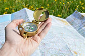 Compass in the hand against a map — Stock Photo