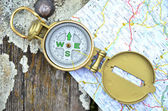 Compass and map on the wooden background — Stock Photo