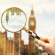 Magnifying glass in the hand against Big Ben — Stock Photo #50996563