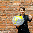 Woman by the wall with world map — Stock Photo