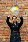 Woman by the wall with world map travel — Stock Photo