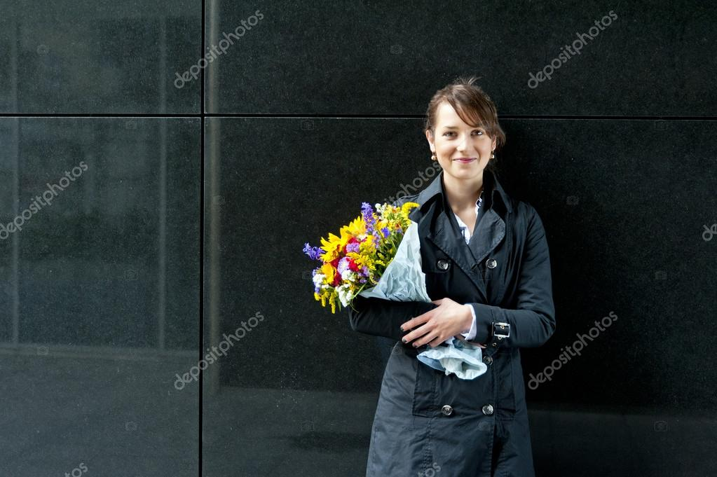 Woman with some flowers on black background — Stock Photo #12756335